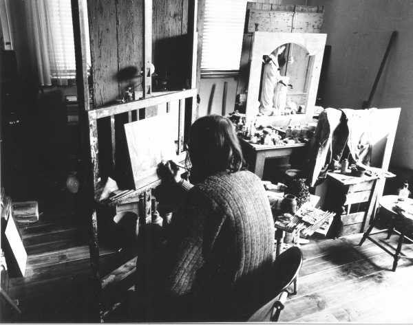 De schilder bezig aan het schilderij Wat overbleef van Oma. Geheel rechts staat een opstelling met heiligenbeeld dat al een jaar niet erg wil vlotten